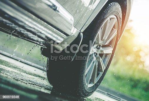 Car Driving in the Rain. Modern Rain Summer Season Tires on the Wet Pavement. Closeup Aquaplaning Photo.