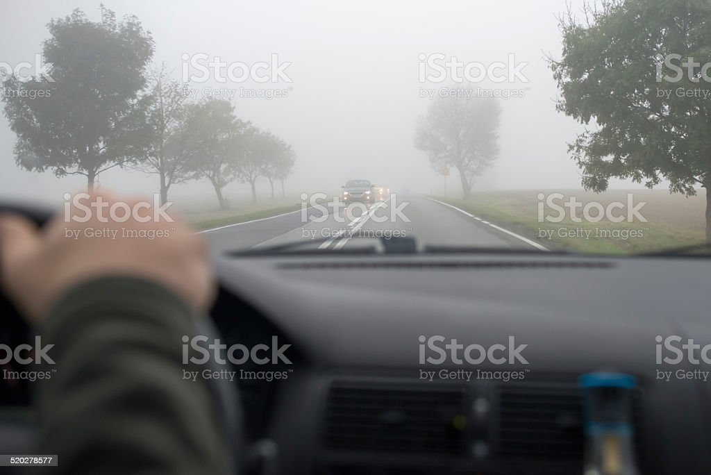 Car driving in thick fog - Royalty-free Asphalt Stock Photo