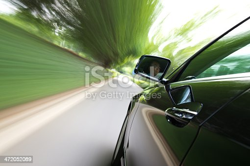 688980174istockphoto A car driving on a country road 472052089