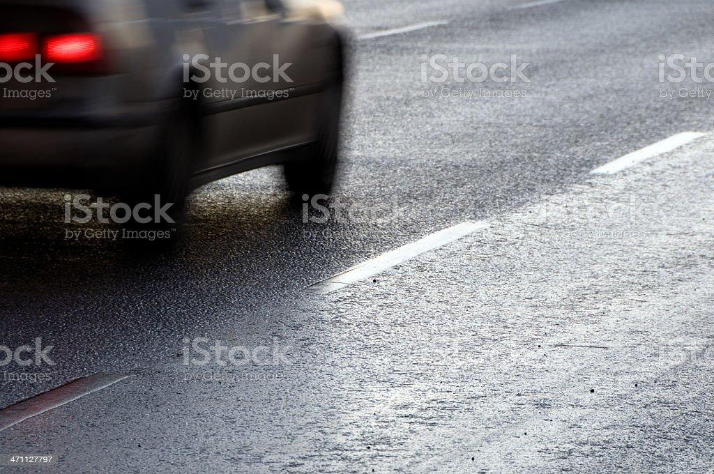 Car driving on a reflecting asphalt road royalty-free stock photo