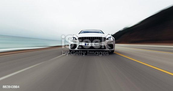 istock car driving on a road by sea 882843864