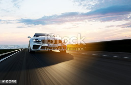 istock car driving on a road by sea 918555756