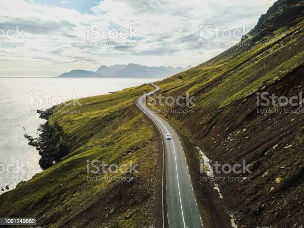 Photo of Car driving on beautiful scenic road in Iceland.