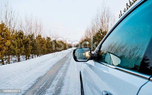 Car driving on country road in winter.