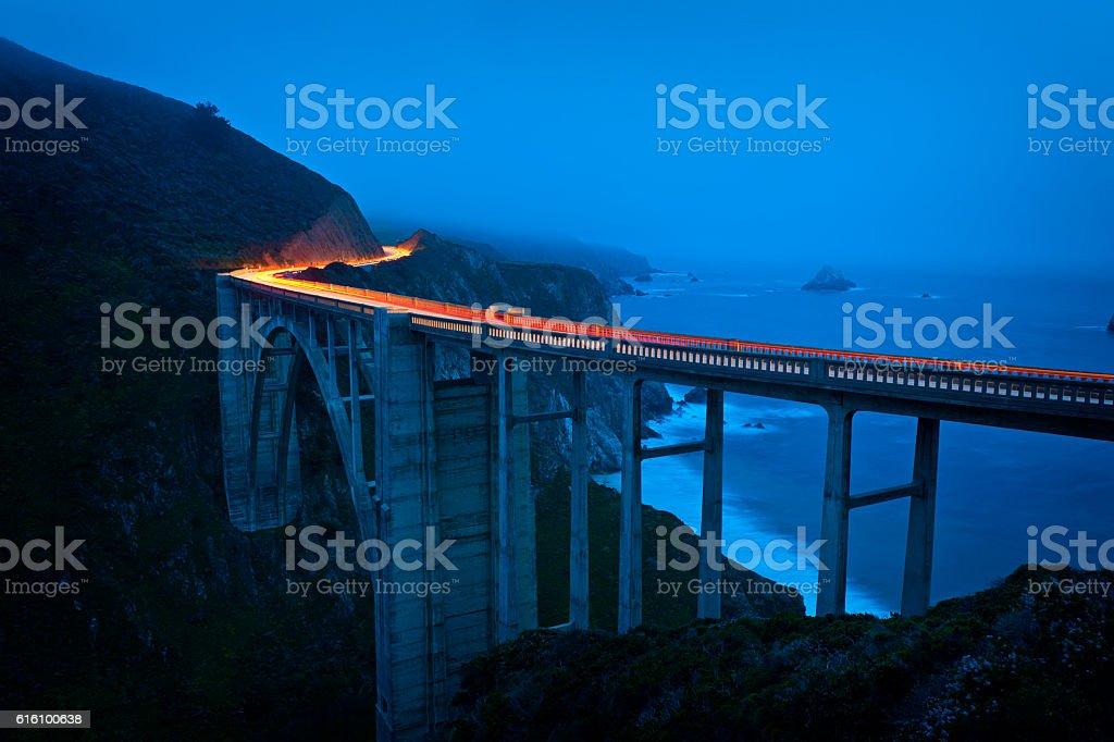 Car driving on large bridge at dusk stock photo