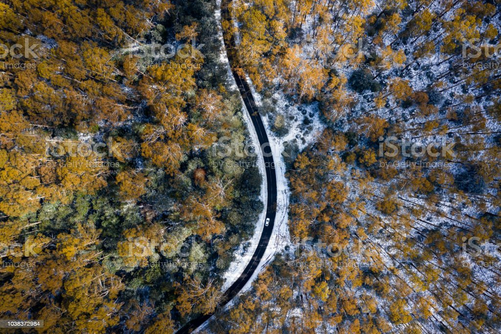 Car Driving on Snow Road Aerial stock photo