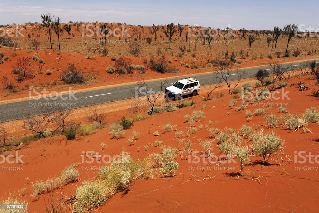 Car Driving on The Road Red Through Australian Outback Landscape stock photo