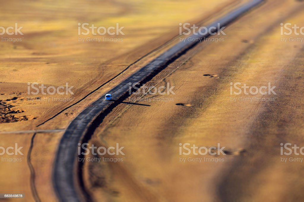 Car driving on winding road in the desert stock photo