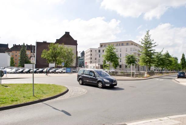 Bloques de un coche conduciendo más allá de una ensambladura en Apartamento barrio residencial en Hoerde Dortmund, Alemania - foto de stock