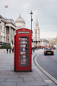 London, UK - April 13, 2019: Car driving past a red phonebox on Pall Mall East, National Gallery on the background. Red phone boxes can be found in current or former British colonies around the world.