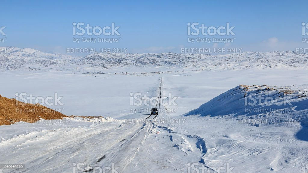 Car driving through a grassland covered in ice and snow in Xinjiang, northen China stock photo