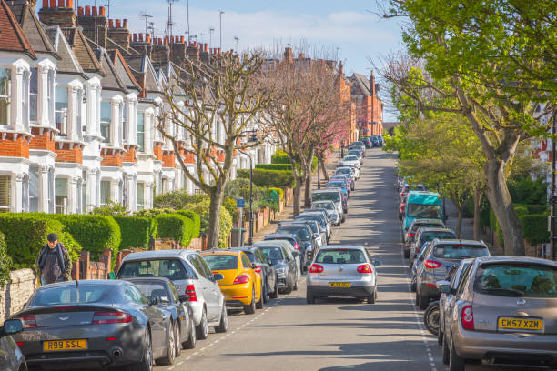 A car driving through a London street lined with terraced houses and parked cars around Crouch End area stock photo