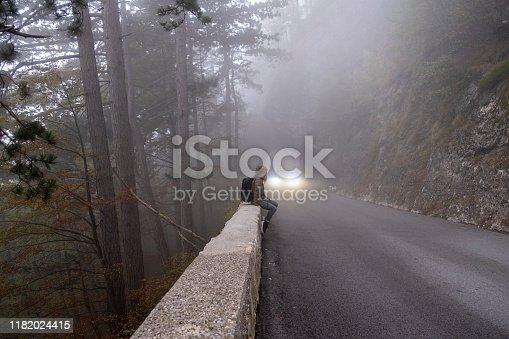 Car driving through a natural stone tunnel in the mountain forest , Predmeja, Slovenia. Europe.