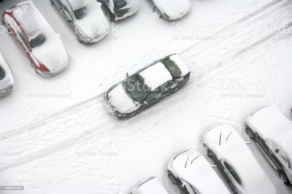 Car Driving Through Snowy Parking Lot royalty-free stock photo