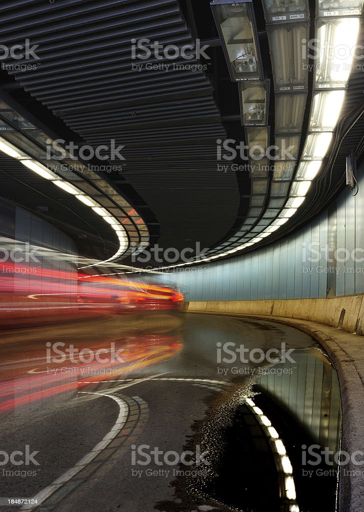 Car driving through wet tunnel by night, diminishing perspective stock photo