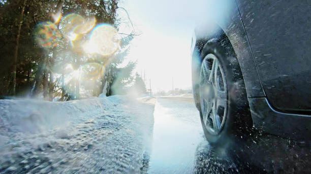 Car Driving Winter tires on snow road close up stock photo