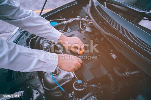 istock Car Engine oil maintenance repair automotive worker.Focusing soft orange image 883571354
