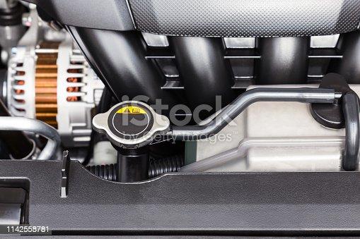 istock Car engine radiator cap and coolant container close-up 1142558781
