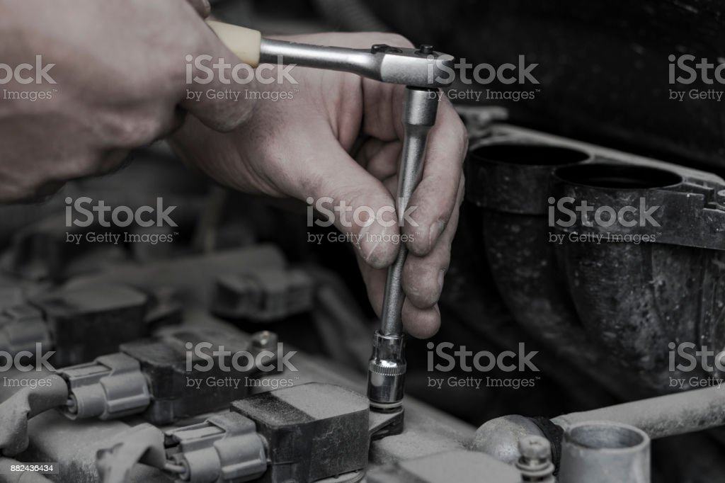 Car engine repair. Replacing the spark plugs in the engine. Repair of the old machine. stock photo