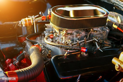 Car engine under hood at sunset