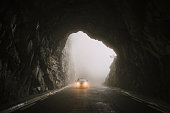A car with lights on, entering a tunnel road