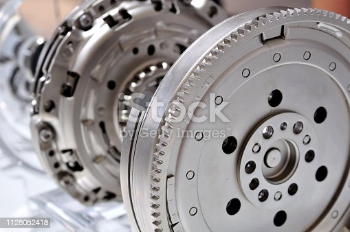 Car flywheel with a clutch in backgroung, with selective focus.