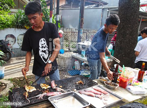Bandung, West Java, Indonesia - December 11, 2016. Car Free Day is held every Sunday morning at the upper end of Jalan Buah Batu in the city of Bandung. People selling grilled squid.