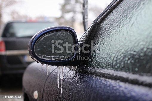 istock Car frozen side mirror after freezing rain 1126859943