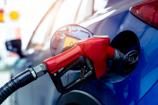 Car fueling at gas station. Refuel fill up with petrol gasoline. Petrol pump filling fuel nozzle in fuel tank of car at gas station. Petrol industry and service. Petrol price and oil crisis concept.