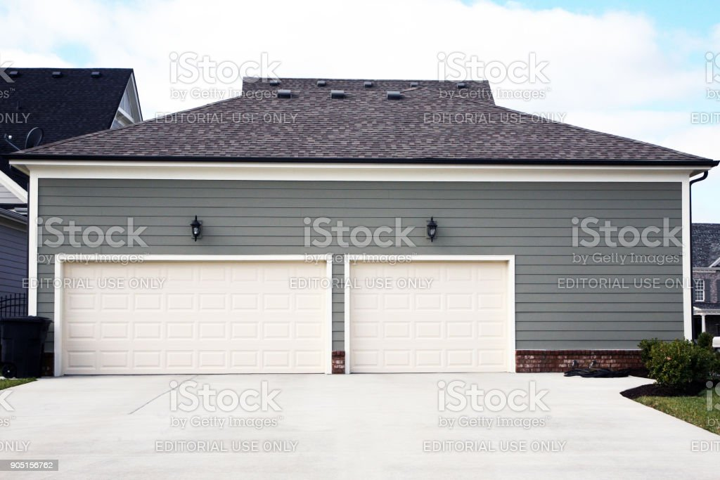 3 car garage attached to a luxury home with prominent driveway stock photo