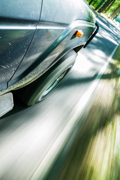Car going fast on road through forest stock photo