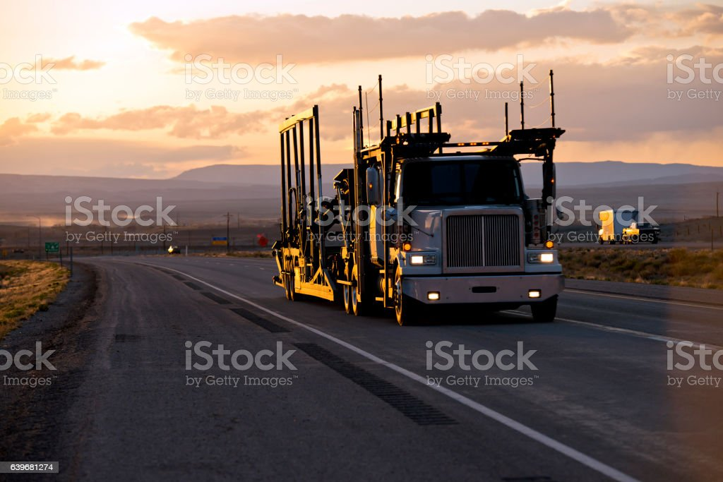 Car hauler semi truck on the road in sunset stock photo