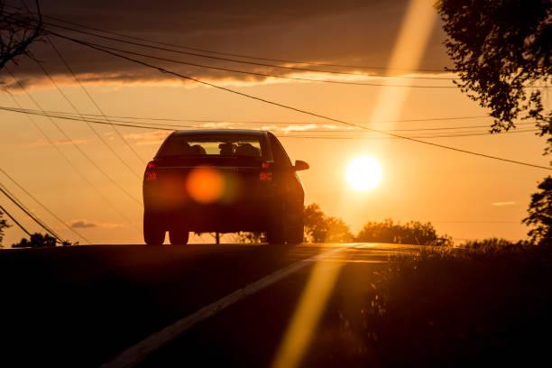 Car heading to sunset stock photo