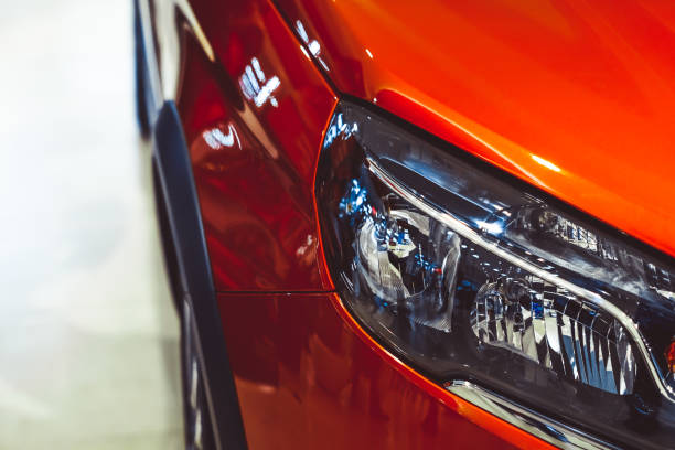 Car headlight in front colorful headlights of white car after the rain at night on car parking headlight stock pictures, royalty-free photos & images
