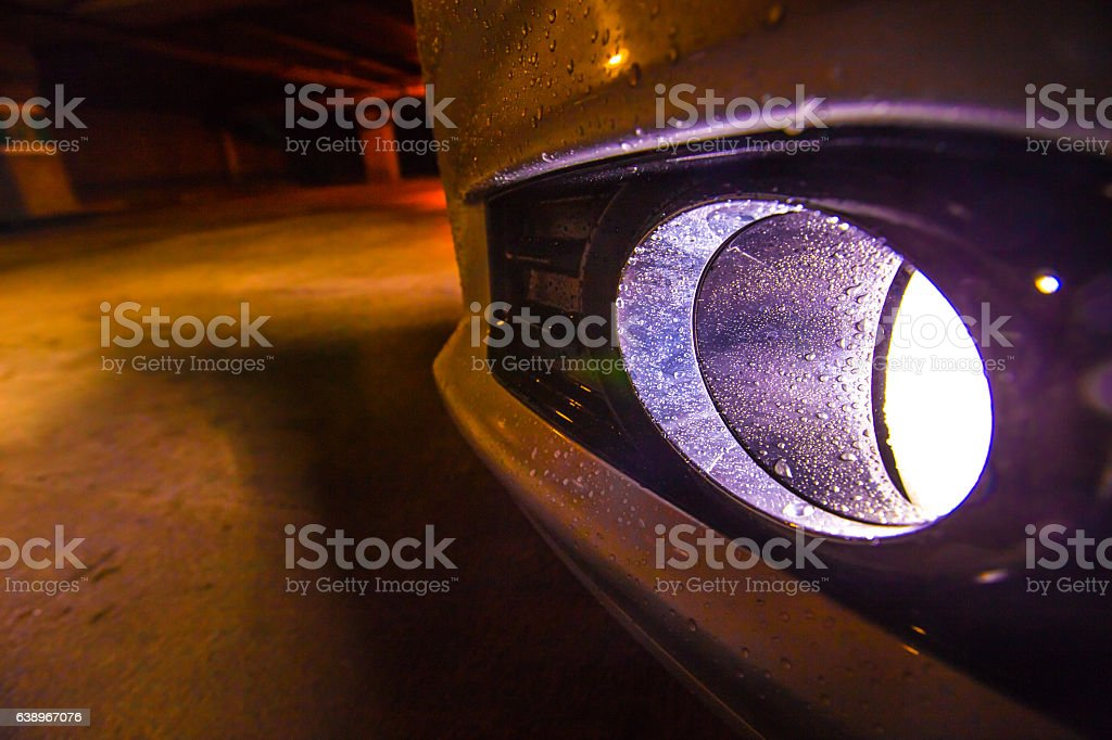 Car headlight on with water dropplets stock photo