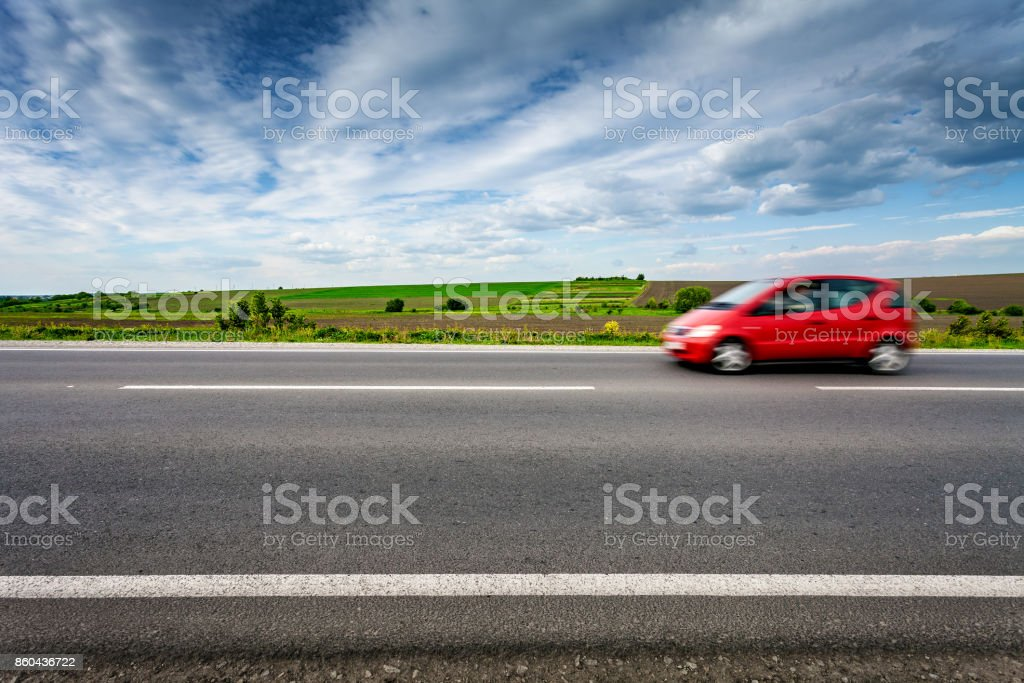 Car in blurred motion on country road, side view. stock photo
