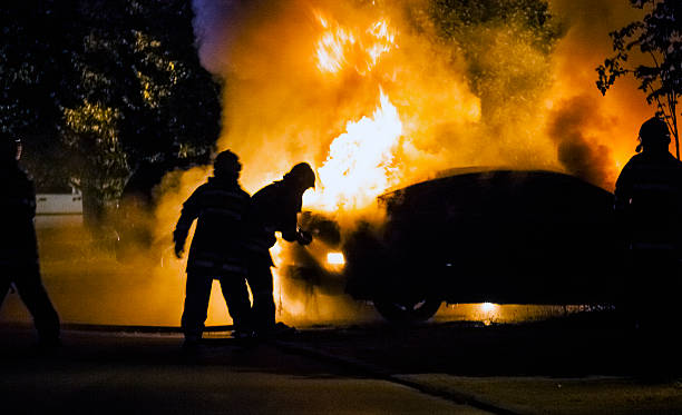 Car in flame Firemen fighting a flaming car during night time terrorism stock pictures, royalty-free photos & images