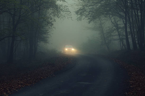 car in fogy night - mist donker auto stockfoto's en -beelden