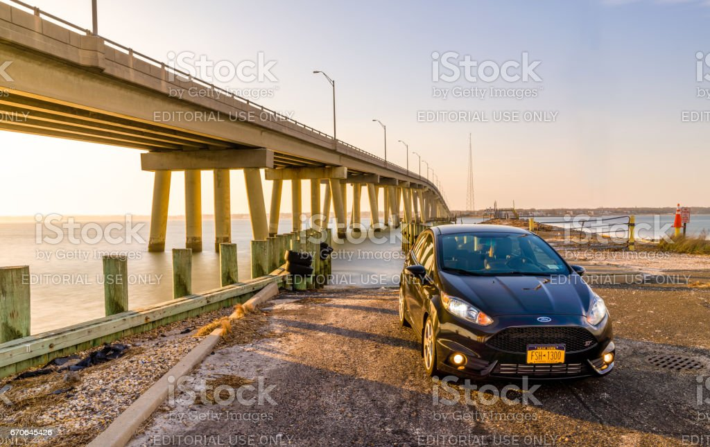 Car in front of a bridge during sunset. stock photo