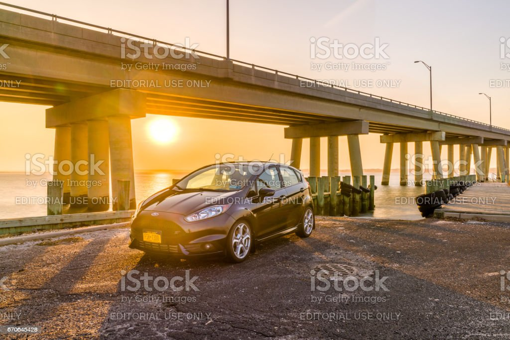 Car in front of a bridge during sunset stock photo
