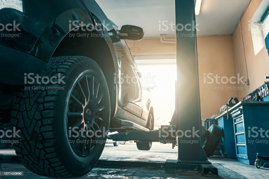 Car in garage of auto repair service shop with special repairing equipment, changing tires stock photo