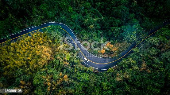 1061550162 istock photo Car in rural road in deep rain forest with green tree forest, Aerial view car in the forest. 1139595108