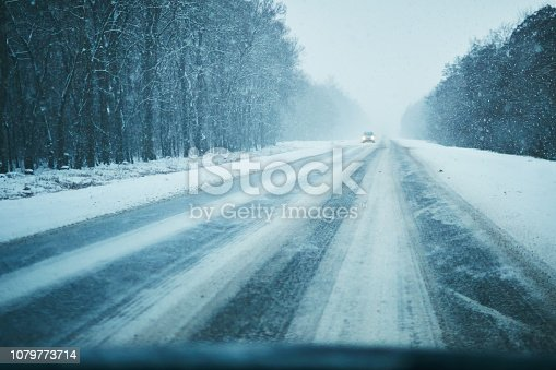 657042754 istock photo Car in storm on a winter road with traffic.  Danger driving in winter. First person view 1079773714
