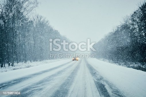 657042754 istock photo Car in storm on winter road with traffic.  Danger driving in winter. First person view 1075951404