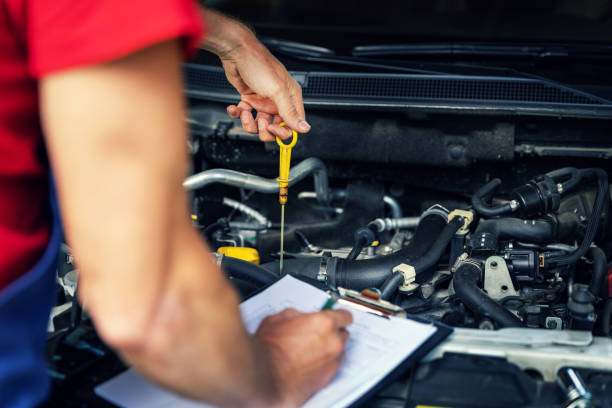 car inspection and maintenance - mechanic check engine oil level and writing in checklist stock photo