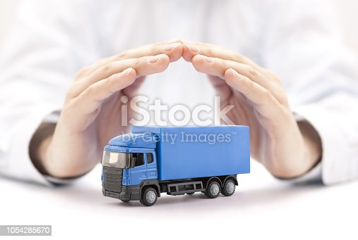 istock Car insurance. Blue truck miniature covered by hands. 1054285670