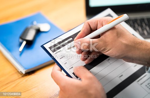 936987338 istock photo Car insurance form, bank loan, lease agreement or repair contract. Man writing personal information to document. Customer buying or salesman selling vehicle. Dealer or rental. 1012049004