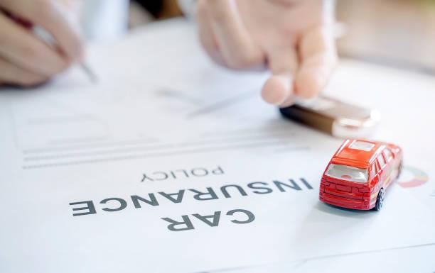 紅色汽車玩具和模糊的人的手形象的汽車保險政策 - 電子摩打 個照片及圖片檔