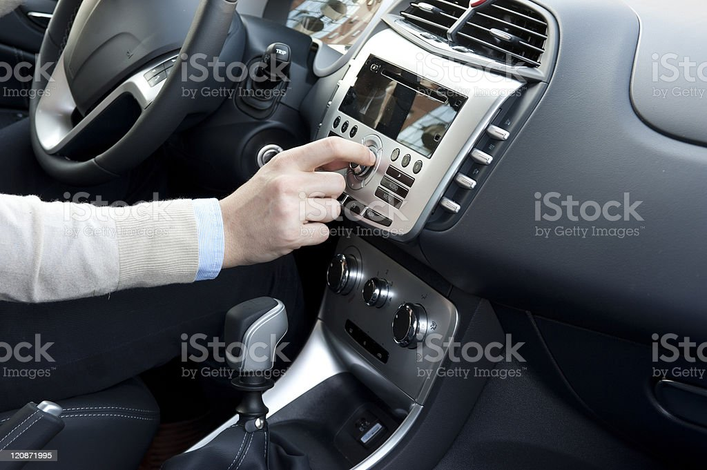 Car interior and hand on the stereo stock photo