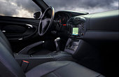 Sports car interior with cloudy sky outside